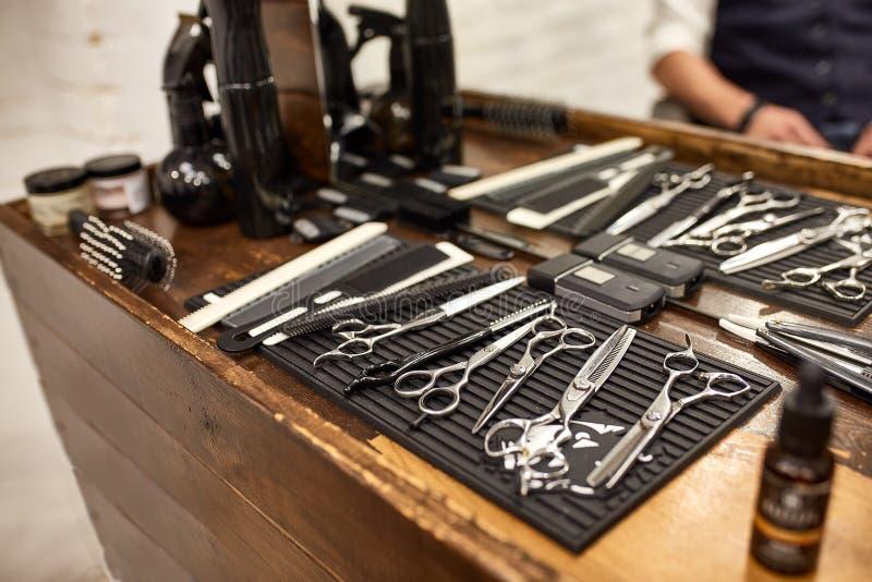 Fryzjer?w m?skich narz?dzia na drewnianej p??ce i lustrze w zak?adzie fryzjerskim zdjęcie stock