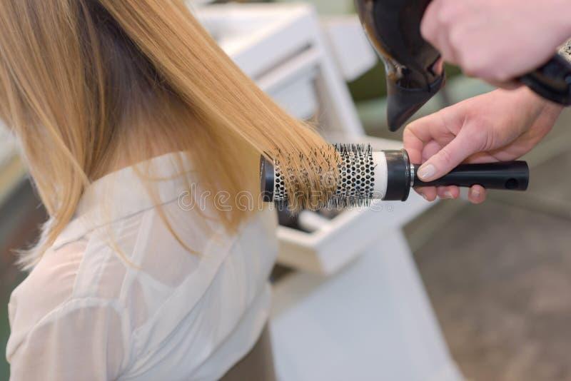 Fryzjer z muśnięciem za młodą kobietą obraz royalty free