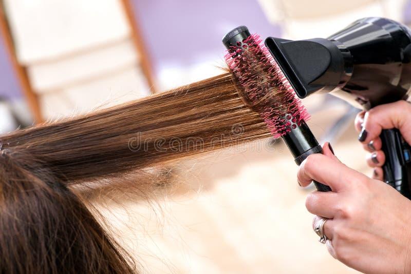 Fryzjera ciosu osuszki długi brown włosy fotografia stock
