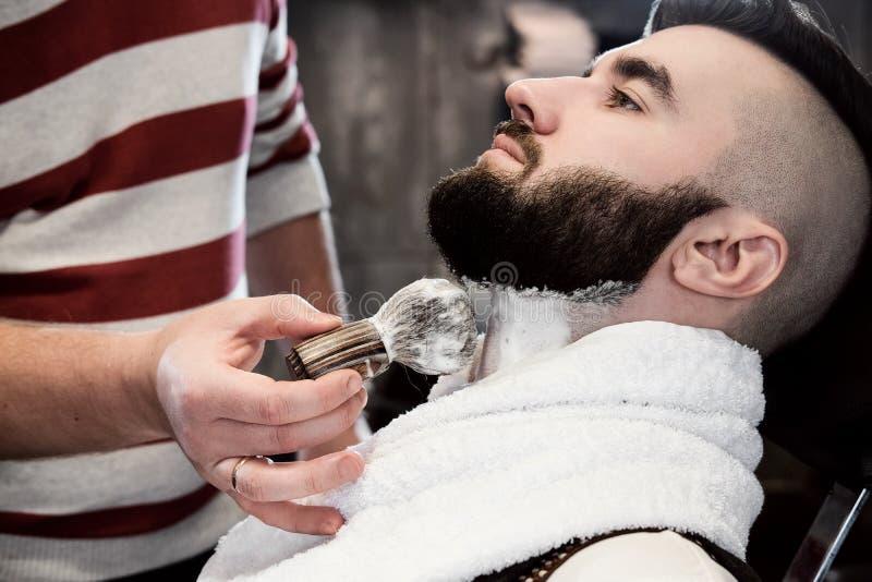 Fryzjera mężczyzna goli klienta z brodą w zakładzie fryzjerskim obrazy stock