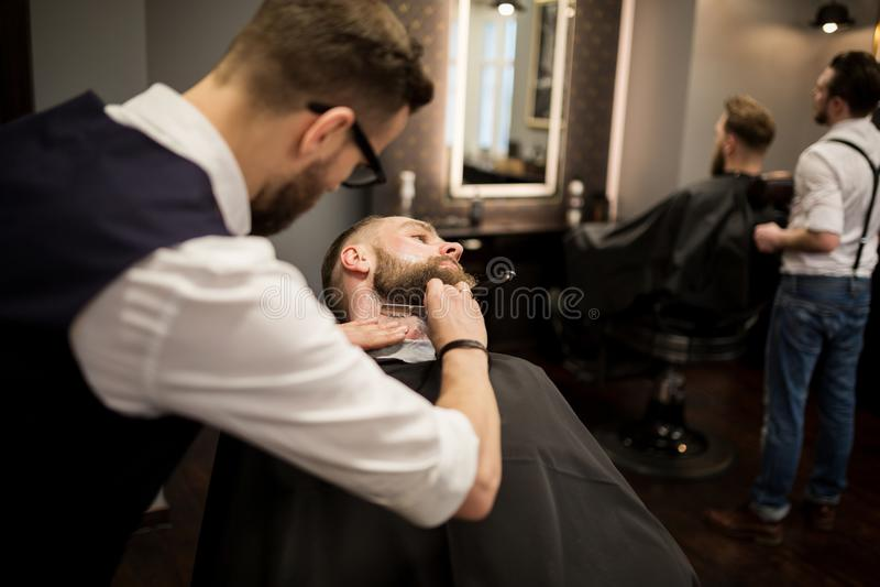 Fryzjera męskiego golenia młody człowiek z żyletką obrazy stock