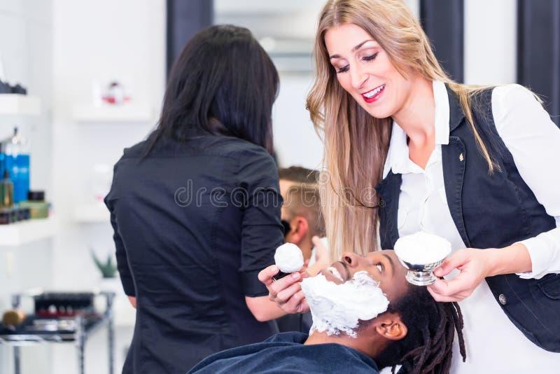 Fryzjera męskiego mydlenia klient golić on zdjęcia stock