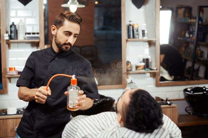 Fryzjera męskiego podesłania pachnidło na kliencie zdjęcie royalty free