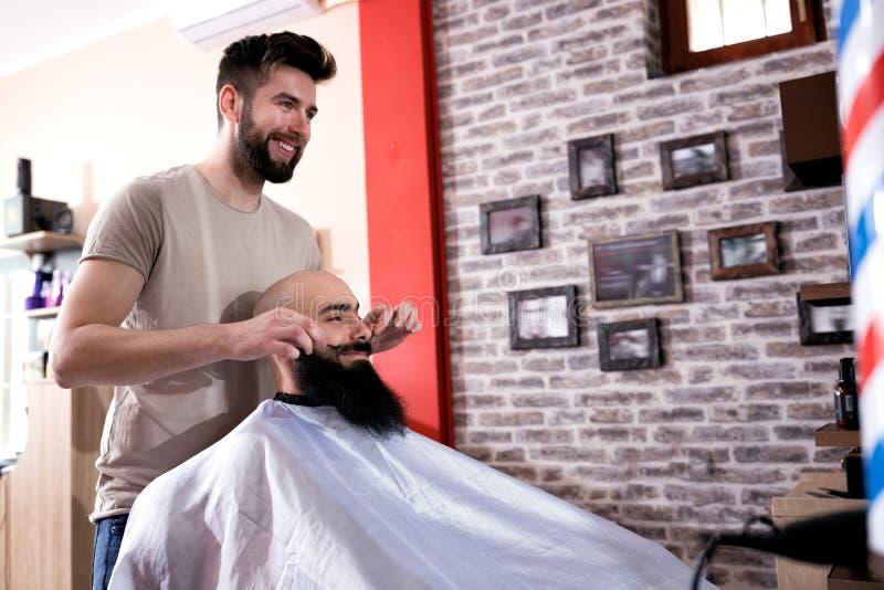 Fryzjera męskiego tytułowania klientów wąsy obraz royalty free