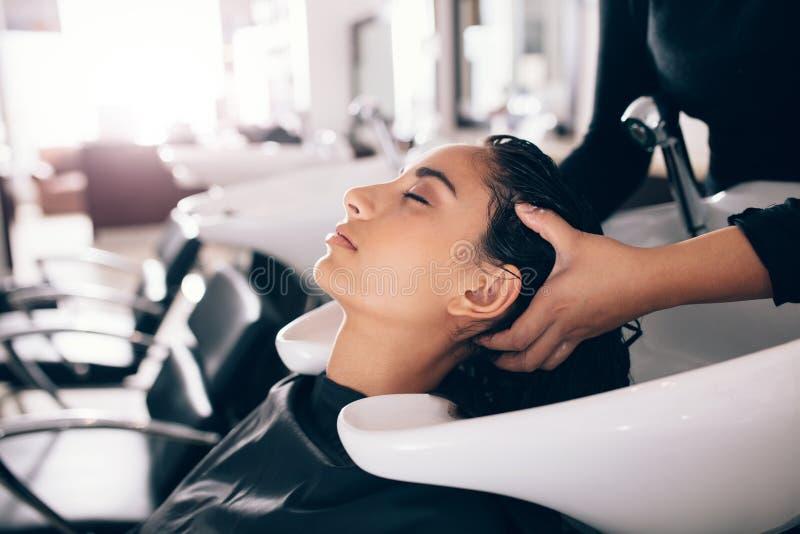 Fryzjera płuczkowy włosy klient przy salonem obraz royalty free