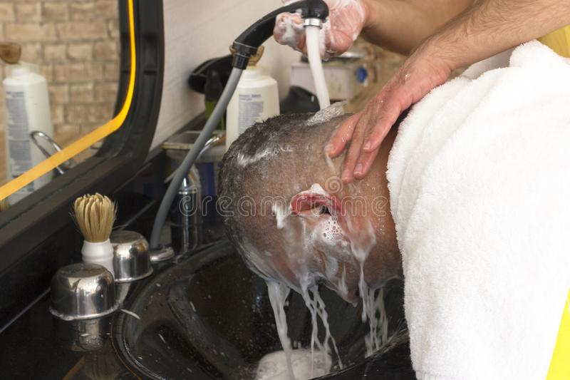 Fryzjera płuczkowy włosy obsługiwać po ostrzyżenia w fryzjera męskiego sklepie zdjęcia stock