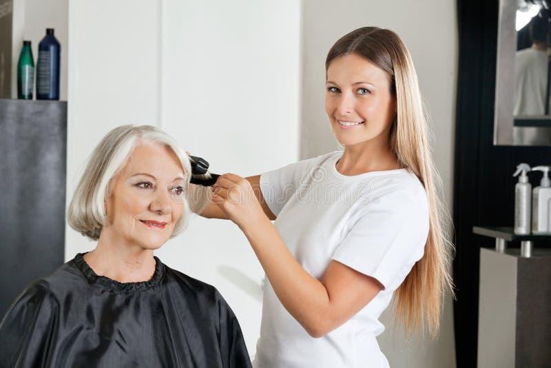 Fryzjera prasowania klienta włosy zdjęcia stock