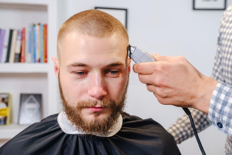 Fryzjerskie dłonie ogolają głowę klienta przycinającą, selektywną ostrością obraz royalty free