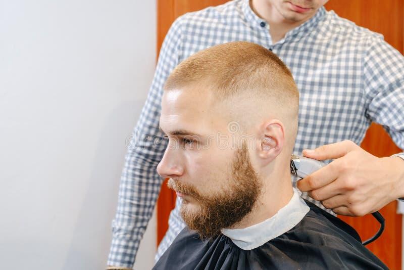 Fryzjerskie dłonie ogolają głowę klienta przycinającą, selektywną ostrością zdjęcie stock