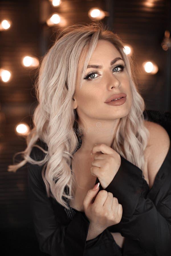 fryzury Piękny blondynki kobiety portret pozuje w czarnej koszula Modny blond dziewczyna model nad bokeh zaświeca ciemnego tło zdjęcia stock