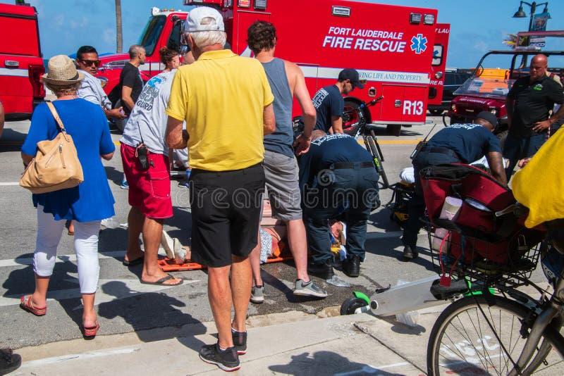 Ft Lauderdale, Florida - Maj 4, 2019: Personer med paramedicinsk utbildning och poliser deltar i till kvinnan som s?rades, d? hon royaltyfri bild