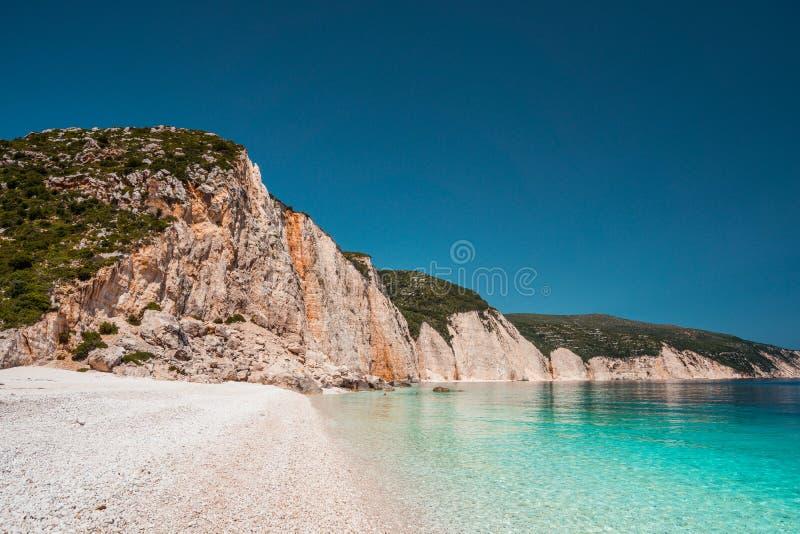 Fteri海滩在Kefalonia海岛,希腊 一有纯净的天蓝色的鲜绿色海的最美丽的未触动过的Pebble海滩 库存图片