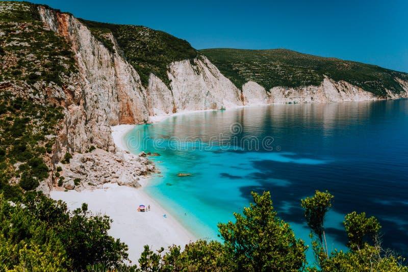 Fteri de surpresa encalha a lagoa, Kefalonia, Grécia Os turistas sob o frio do guarda-chuva relaxam perto do mar esmeralda azul c imagens de stock royalty free
