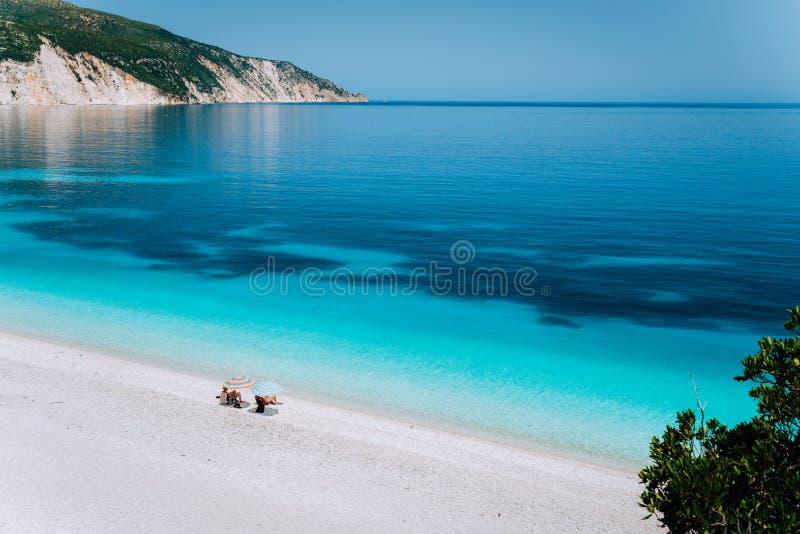 Fteri strand, Kefalonia, Grekland Det ensamma oigenkännliga turist- parnederlaget från kyla för solparaply kopplar av nära frikän royaltyfria bilder