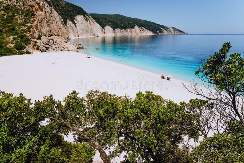 Fteri-Strand, Kefalonia, Griechenland Einsame Touristen unter Regenschirmschauer entspannen sich nahe klarem blauem Smaragdtürkis stockbilder