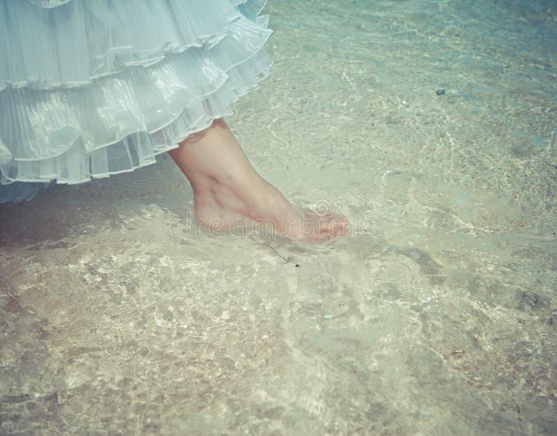 Fuß der Braut berührt Wasser im Meer, mit einem Retro- Effekt stockfotos