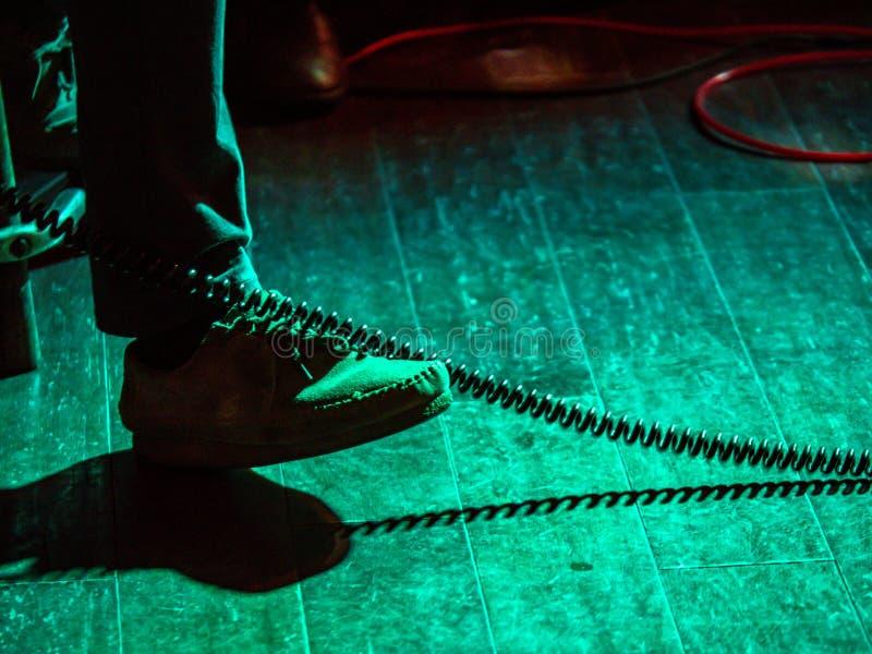Fuß, der im Rhythmus der musikalischen Leistung in einem schwach beleuchteten Stadium klopft stockbilder