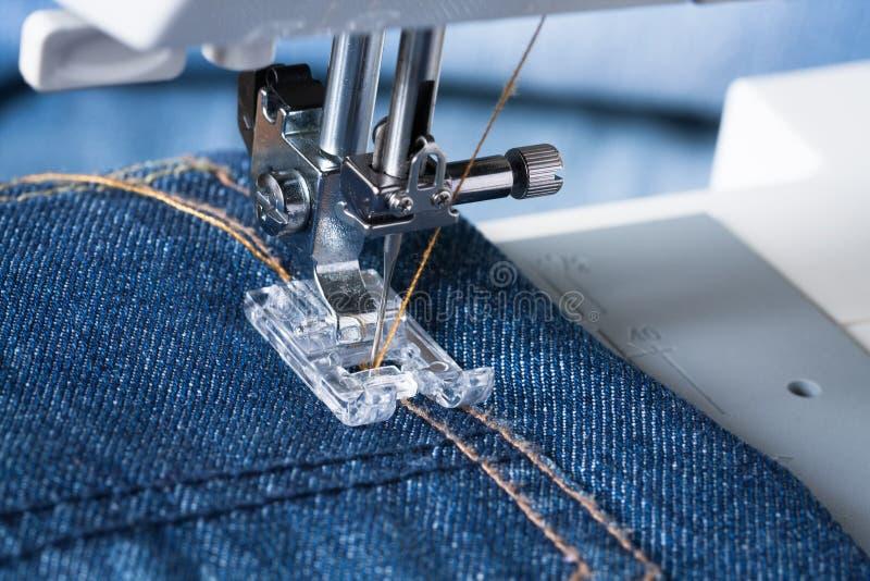 Fuß der Nähmaschine auf Jeans-Gewebe stockfotos
