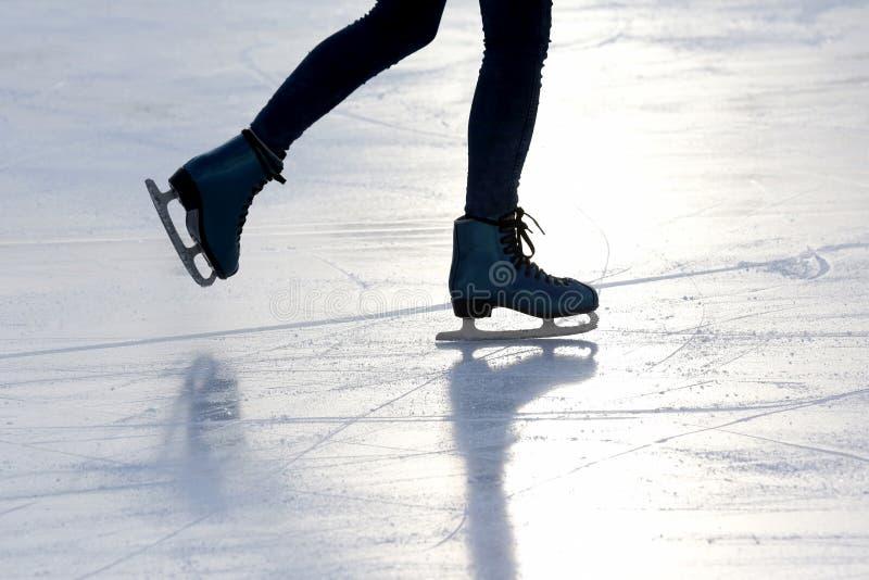 Fuß Person auf der Eisbahn im Sonnenlicht Schlittschuh laufend lizenzfreie stockbilder