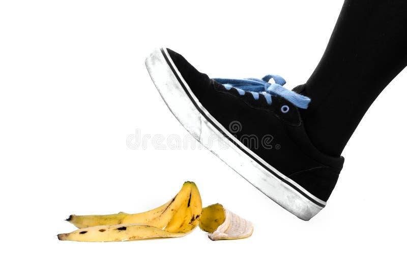 Fuß, Schuh ungefähr, zum auf Bananenschale zu gleiten stockfotografie