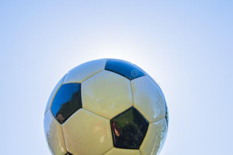 Fußball auf dem Hintergrund der Sonne lizenzfreie stockfotos
