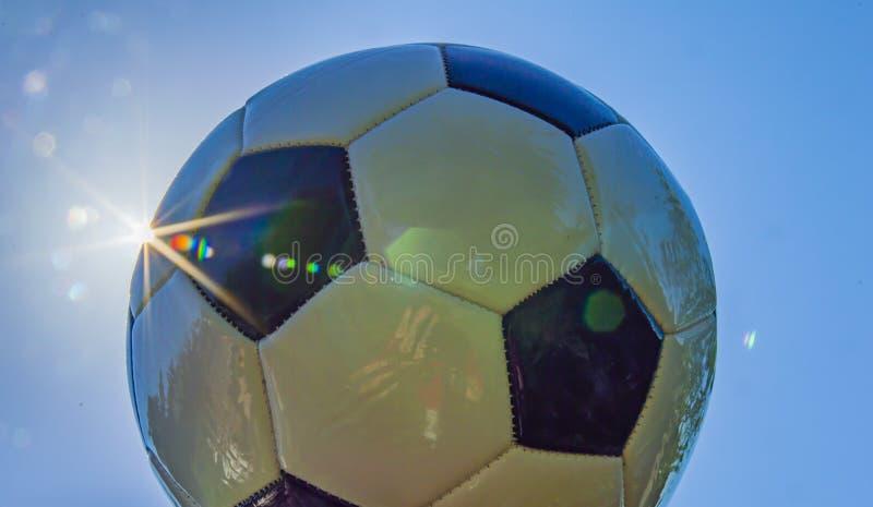 Fußball auf dem Hintergrund der Sonne lizenzfreie stockbilder