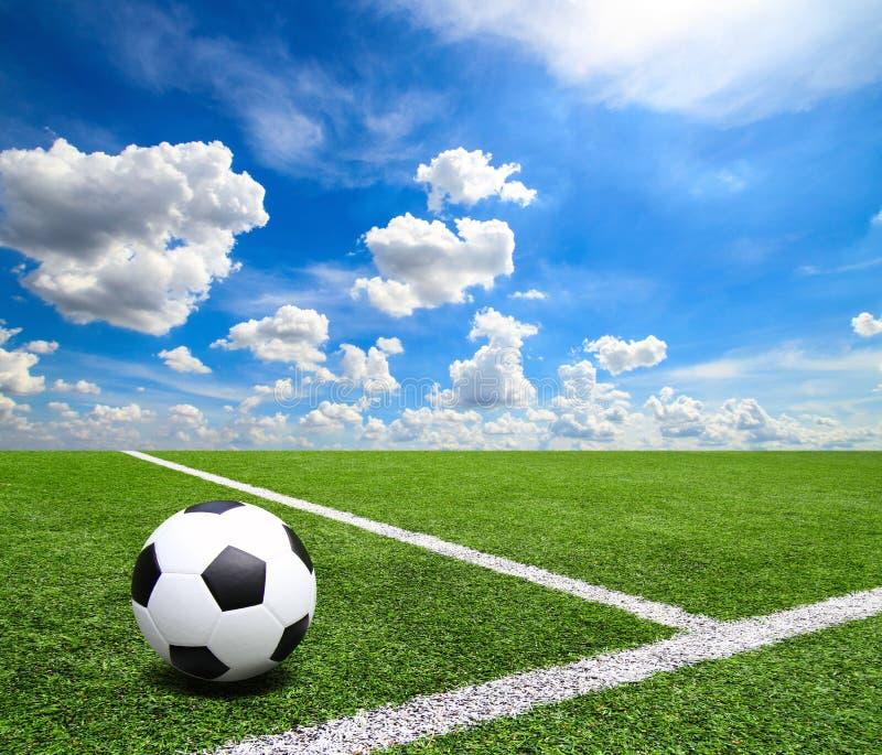 Fußball und Fußballplatz bedecken Hintergrund des blauen Himmels des Stadions mit Gras lizenzfreie stockfotografie