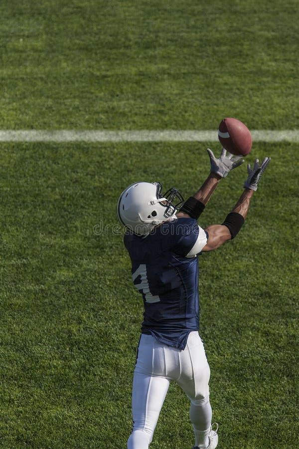 Fußballaktionsfoto des Athleten einen Touchdown-Pass fangend lizenzfreies stockbild