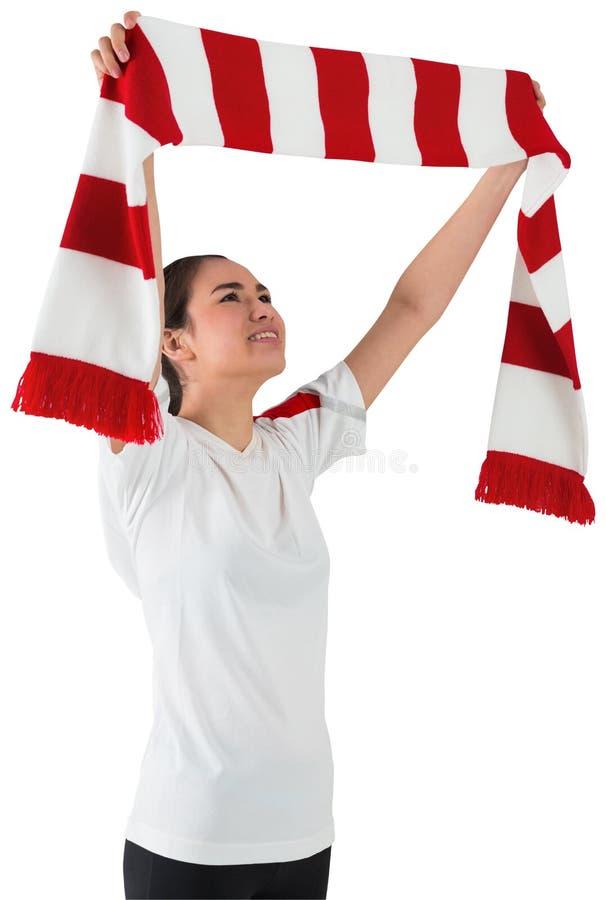 Fußballfan, das roten und weißen Schal wellenartig bewegt lizenzfreies stockfoto