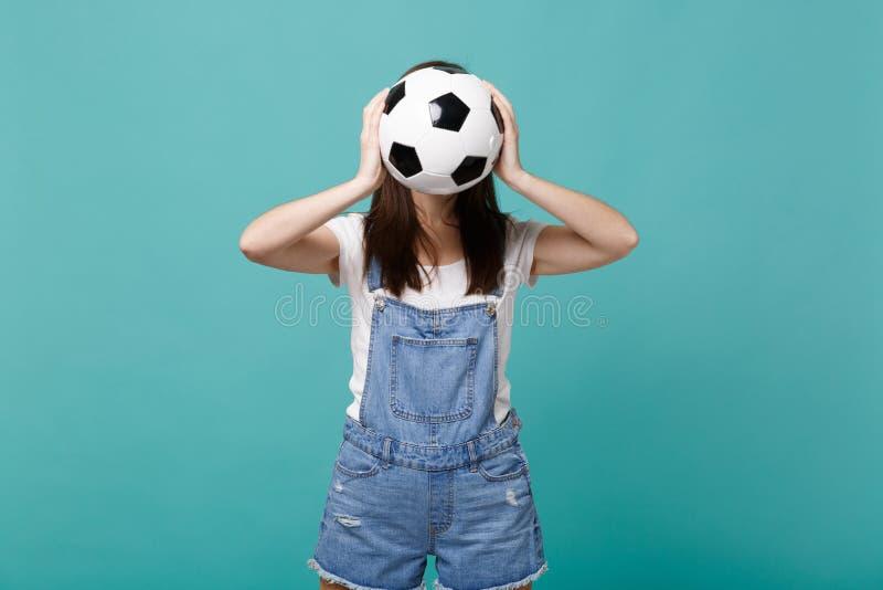 Fußballfanbeifall der jungen Frau herauf Stützlieblingsteambedeckungsgesicht mit dem Fußball lokalisiert auf blauer Türkiswand lizenzfreies stockbild