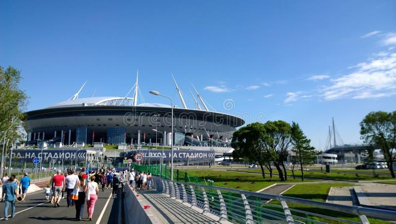 Fußballfane, die in Richtung zum Stadion im sonnigen Tag des Sommers in St Petersburg vorangehen stockfotografie