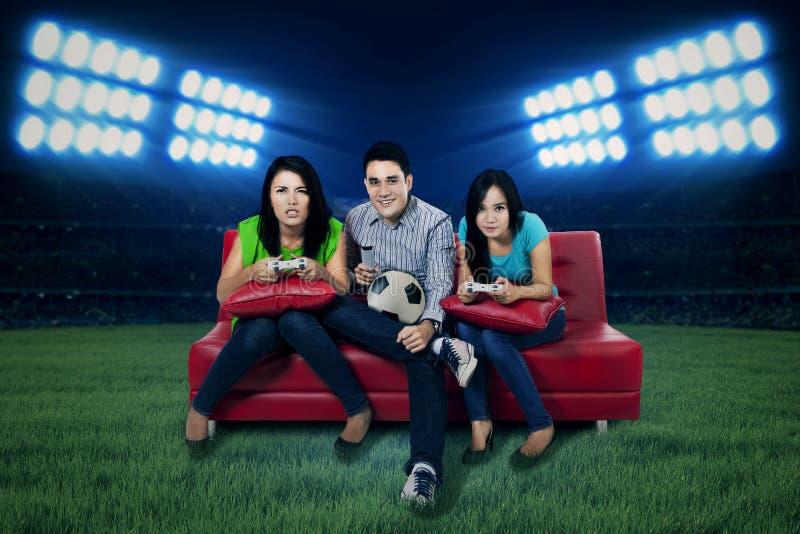 Fußballfans, die Fußballspiel spielen lizenzfreie stockfotos