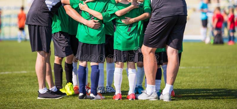 Fußballfußballspiel für Kinder Trainer, der junge Fußballteamanweisungen erteilt Jugendfußballteam zusammen vor Endspiel lizenzfreies stockfoto