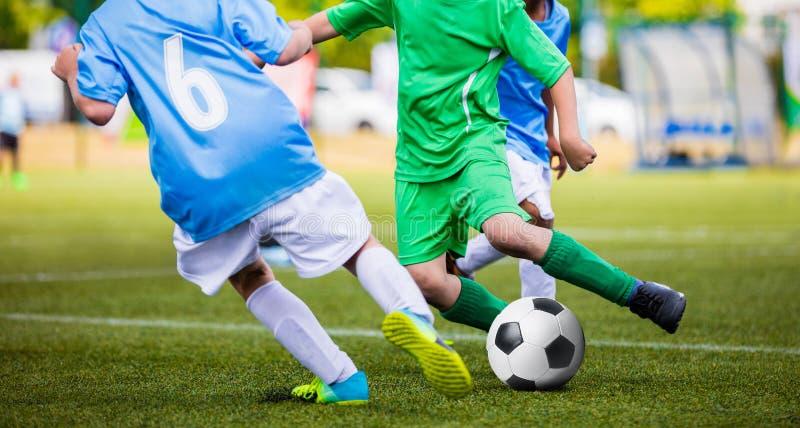 Fußballfußballspiel Young Boys, das Fußball-Ball auf der Sport-Neigung tritt stockfotografie