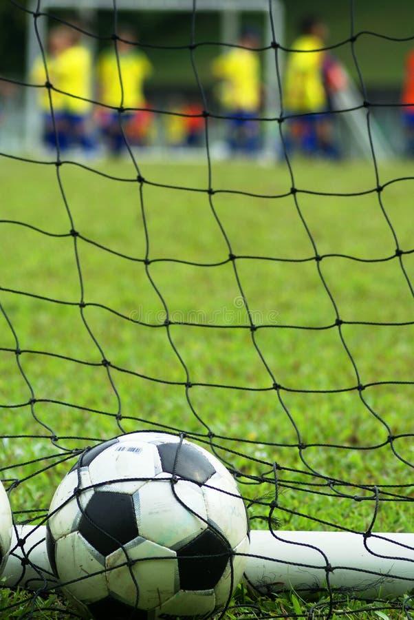 Fußballkugel im Netz am Feld stockbilder