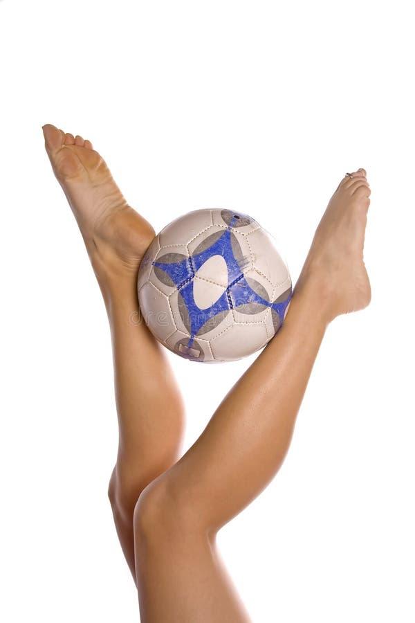 Fußballkugel- und -Frauenfahrwerkbeine stockfotos