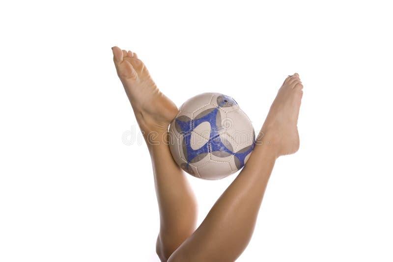 Fußballkugel zwischen womans Füßen stockbild