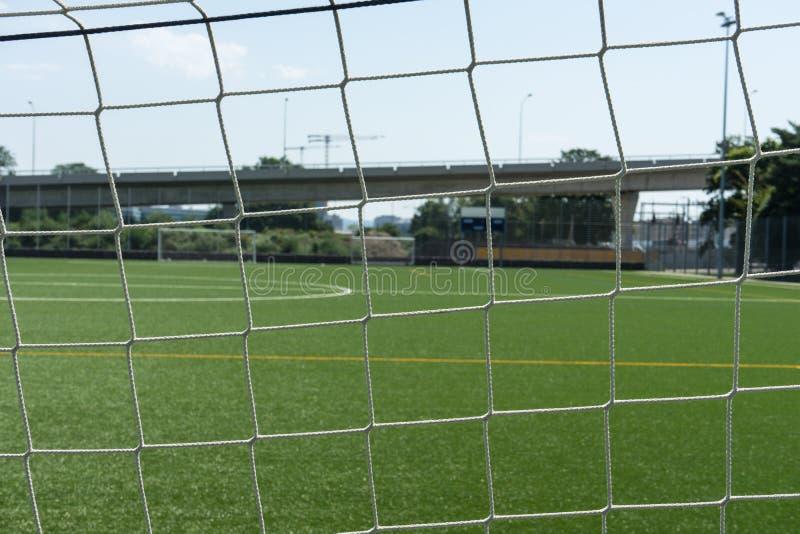Fußballplatz gesehen durch Netz stockbild