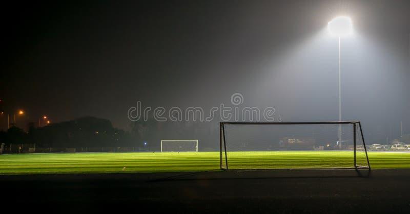 Fußballplatz nachts und mit Scheinwerfer lizenzfreie stockfotos
