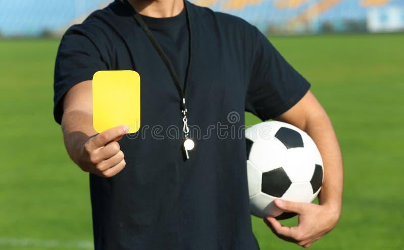 Fußballschiedsrichter, der gelbe Karte am Stadion zeigt stockfotografie