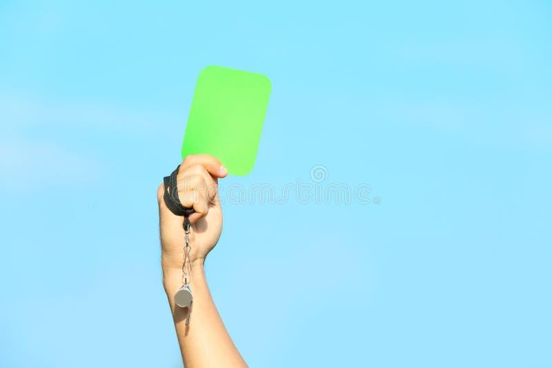Fußballschiedsrichter-Vertretungsgreen card gegen blauen Himmel stockbilder