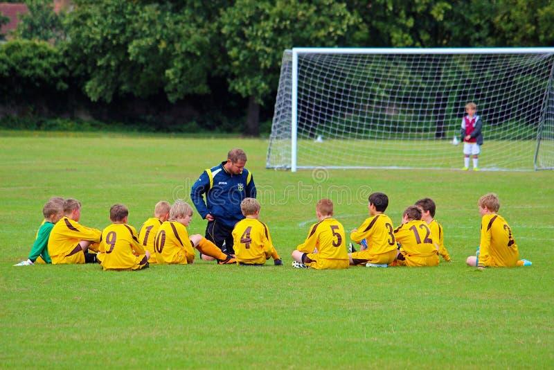 Fußballsitzung der Kinder vor dem Spiel lizenzfreie stockfotografie