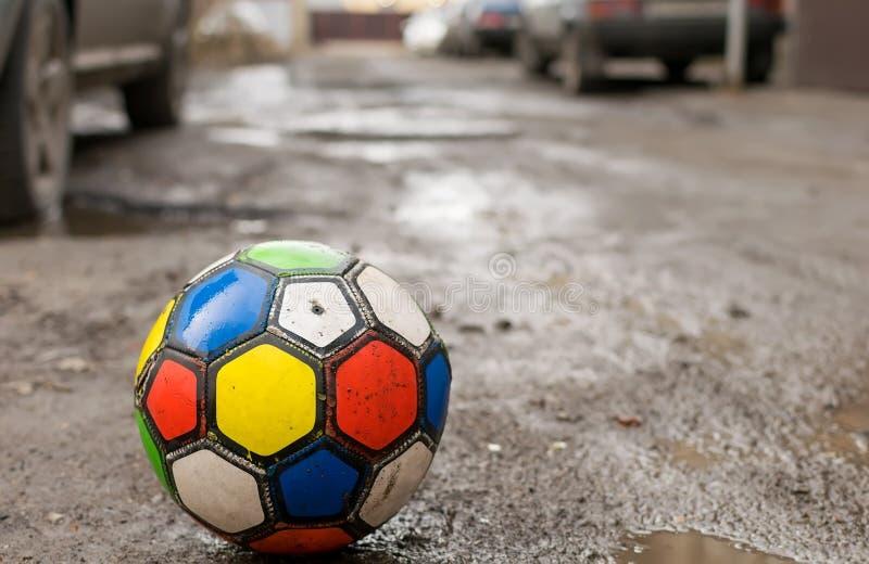 Fu?ballspiel der Kinder ist auf einer schmutzigen defekten Stra?enstra?e unter Pf?tzen und Wohnyards H?usern stockbilder