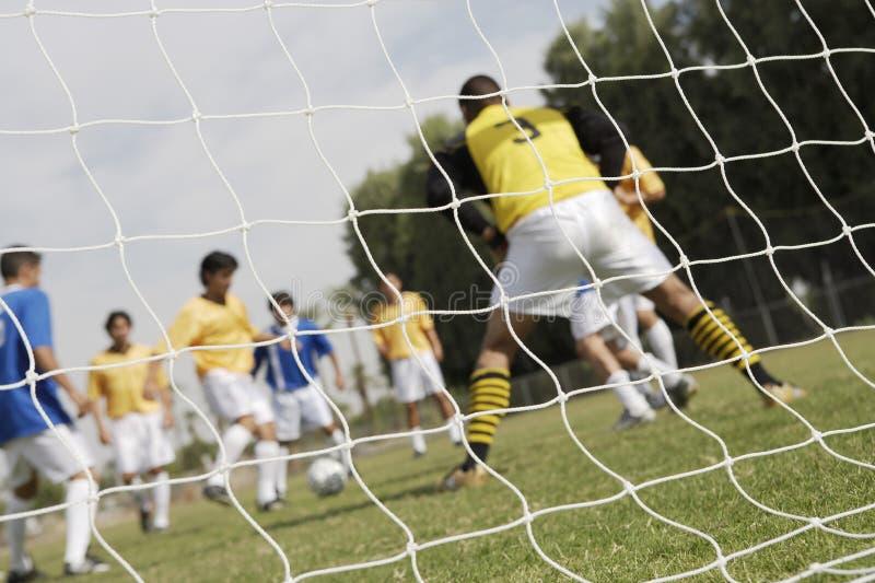 Fußballspiel gesehen durch Netz lizenzfreies stockbild