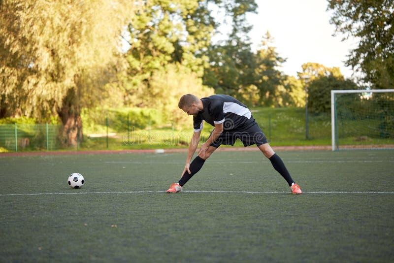 Fußballspieler, der Bein auf Feldfußball ausdehnt stockfotografie