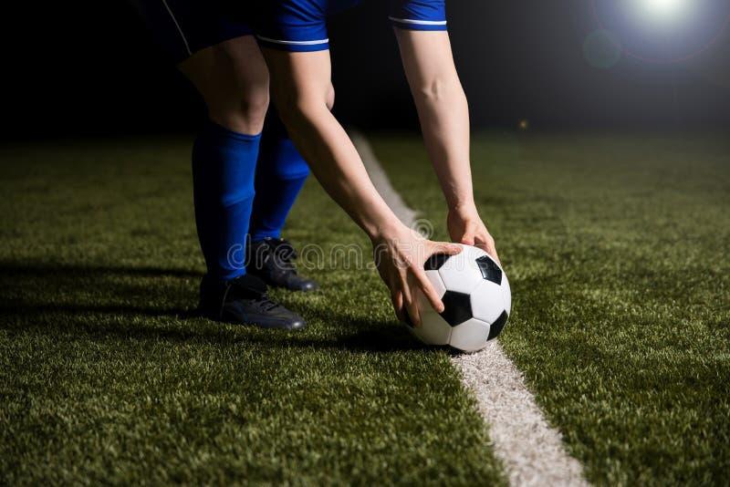 Fußballspieler, der den Fußball auf Mittellinie setzt stockfoto