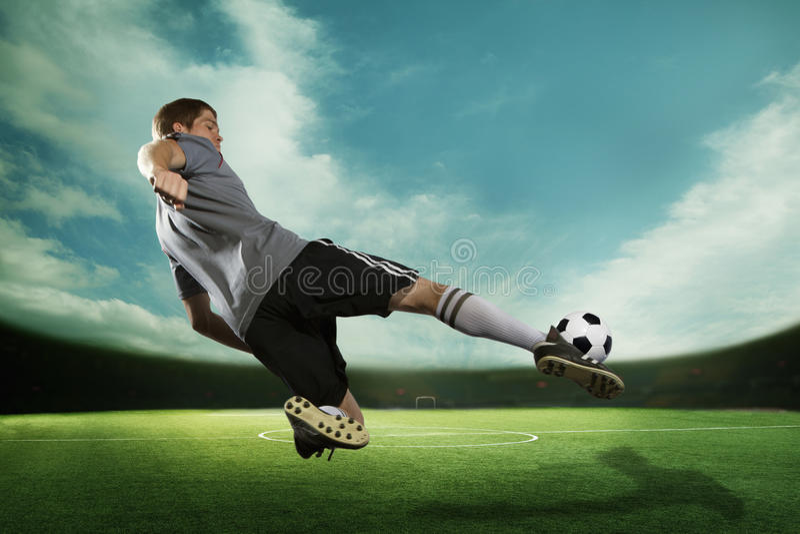 Fußballspieler, der den Fußball in der mittleren Luft, im Stadion mit dem Himmel tritt lizenzfreies stockfoto