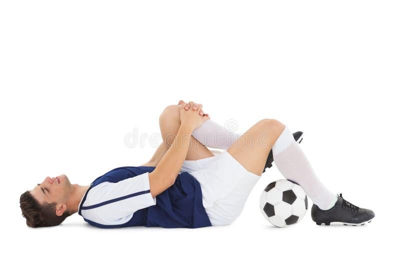 Fußballspieler, der unten verletzt liegt lizenzfreie stockfotografie