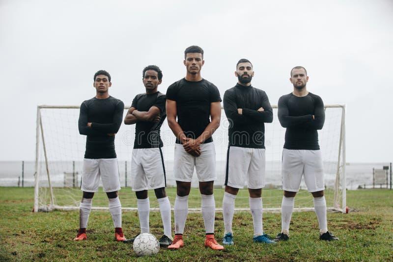 Fußballspieler, die auf einem Fußballplatz vor Torpfosten stehen stockfotos