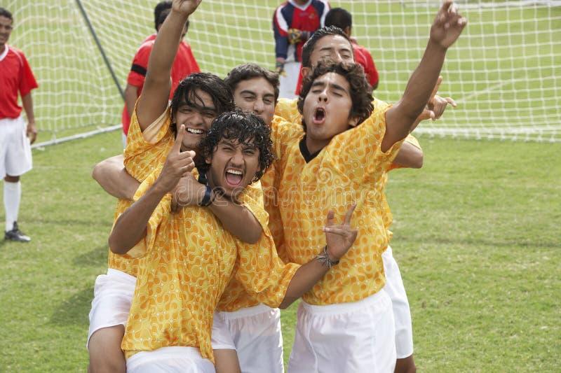Fußballspieler, die ihren Sieg feiern lizenzfreie stockfotografie